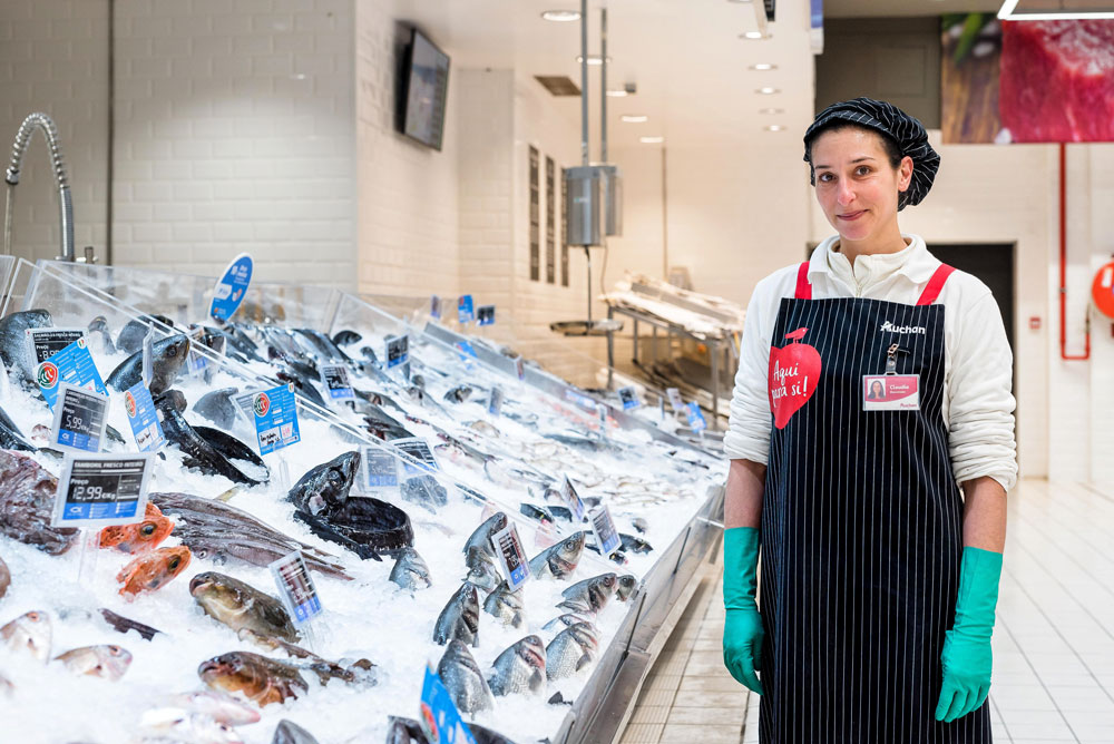 Auchan Team member next to fresh fish